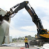 An excavator with a shearing mechanism attached, operated by a member of JDC Demolition, rips into the outer wall of the B5 tank, an old oil tank inside the Salem Power Plant facility on Wednesday afternoon. The B5 tank is the first of the old oil tanks on the site to be taken down and will take approximately two weeks until it is completely gone. DAVID LE/Staff photo. 7/30/14.