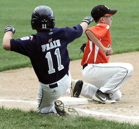 KEN YUSZKUS/Staff photo. Beverly's 3rd baseman Nick McIntyre gets the throw, but Hamilton Wenham's Will Frain is safe after running back to 3rd during the Williamsport Little League District 15 tournament game against Hamilton Wenham.  7/7/14