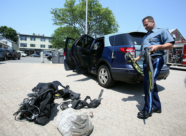 A Massachusetts State Police diver prepares his gear to assist in the search for a missing diver off Children's Island in Marblehead on Tuesday afternoon. DAVID LE/Staff photo. 7/22/14.