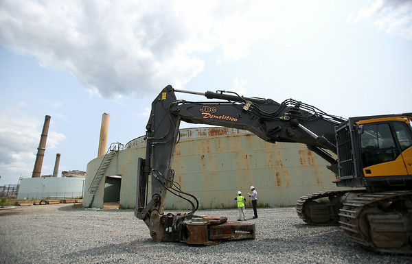 An excavator with a shearing tool attached to the end sits next to the B5 Oil Tank inside the Salem Power Plant as it waits to tear down the old tank. B5 was the first of the tanks to be taken down. DAVID LE/Staff photo. 7/30/14.