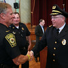 Newly sworn-in Peabody Police Chief Tom Griffin, right, shakes hands with Peabody Police Lieutenant Scott Wlasuk, after a swearing-in ceremony inside the Wiggin Auditorium at City Hall on Thursday afternoon. DAVID LE/Staff photo. 7/24/14.