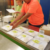 Lily Cuzner, left, and Christopher Romero, Danvers Recreation staff members prepare meals of celery and ranch dressing for the kids participating in a summer program at the Smith School on Tuesday afternoon. KEN YUSZKUS/Staff photo.    7/8/14