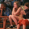 Artworks at Waring campers Jerry Odoku, 11, Julianna Saunders, 10, and Rowan Mulder, 9, intently watch and laugh during a Circus Major performance on Thursday afternoon. DAVID LE/Staff photo. 7/17/14.