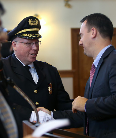 Peabody Police Chief Tom Griffin, left, shakes hands with Mayor Ted Bettencourt, right, after being sworn into office on Thursday afternoon. DAVID LE/Staff photo. 7/24/14.