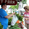 Marilyn Limongiello, of Peabody, gets a fresh bag of vegetables from Nick Srybmy, of Hereford Valley Farm in Andover, at the Peabody Farmer's Market on Tuesday afternoon. DAVID LE/Staff photo. 7/15/14.