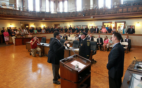 Peabody Chief of Police Tom Griffin, right, raises his right hand while being sworn into office by Peabody City Clerk Tim Spanos, left, in front of a packed house inside the Wiggin Auditorium at City Hall on Thursday afternoon. DAVID LE/Staff photo. 7/24/14.