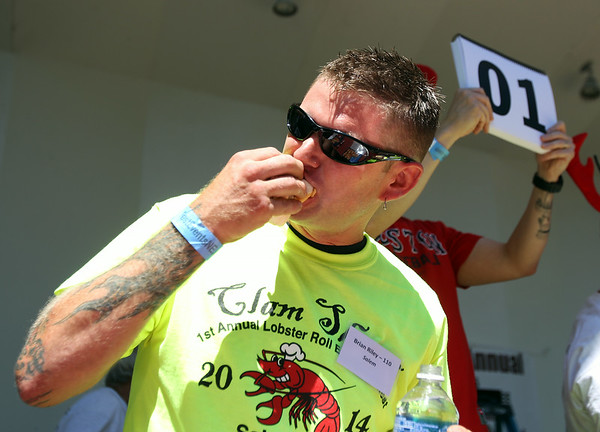 Brian Riley, of Salem, takes a large bite out of a lobster roll during the Lobster Roll Eating Contest during the first Salem Willows Seafood Festival on Saturday afternoon. DAVID LE/Staff photo. 7/12/14.