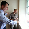Peabody Mayor Ted Bettencourt, left, talks about the beautiful view of Peabody Square with Norman Lee, of Northeast Contractor Solutions Inc., inside one of the ten new apartment units at 17 Main Street in Peabody. The ten units are made up of eight 1-bedroom apartments and two studio apartments, and replaced the old Masonic Lodge which was vacant for over twenty years. DAVID LE/Staff photo. 7/31/14.
