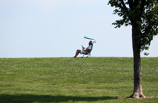 A man sits under the shade of his chair while reading at Dane Street Beach on Wednesday afternoon. DAVID LE/Staff photo. 7/23/14.