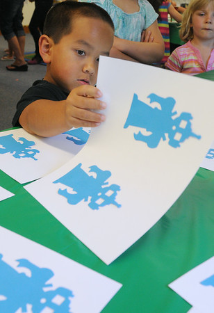 KEN YUSZKUS/Staff photo. Franklin Soon, 6, of Salem plays the Mad Matching game at the Fizz, Boom, Party held at the Salem Public Library. 7/1/14