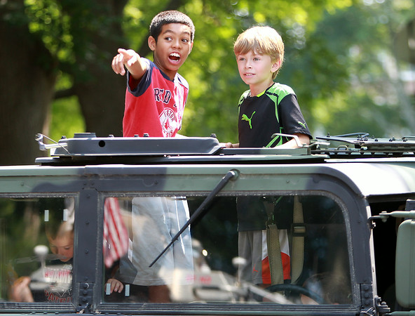 Eleven-year-old Jayden Halecki, left, and ten-year-old Cody Dailey, enjoy the view from the sunroof of a military vehicle during a Vehicle Day at the Ipswich Public Library on Friday morning. DAVID LE/Staff photo. 7/25/14.