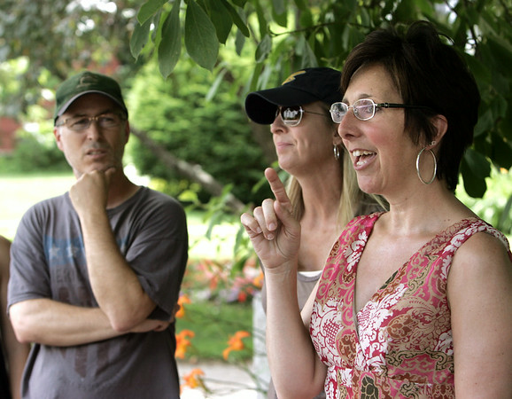 KEN YUSZKUS/Staff photo.  From left, Perry and Kerry Scofield of California and Kelly Hiselman of Essex talk about preserving first period homes and other historic structures in downtown Ipswich.  7/10/14