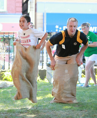 Seven-year-old Nathan Allder, left, races Boston Bruins prospect Alex Globke, right, in a sack race on Friday afternoon at the Peabody Institute Library. DAVID LE/Staff photo. 7/11/14.
