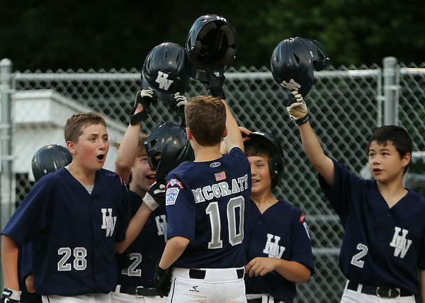 Hamilton-Wenham pitcher Cooper McGrath (10) is greeted at home plate after launching a two-run homer in the top of the 3rd inning on Thursday evening at Harry Ball Field in Beverly. DAVID LE/Staff photo. 7/10/14.