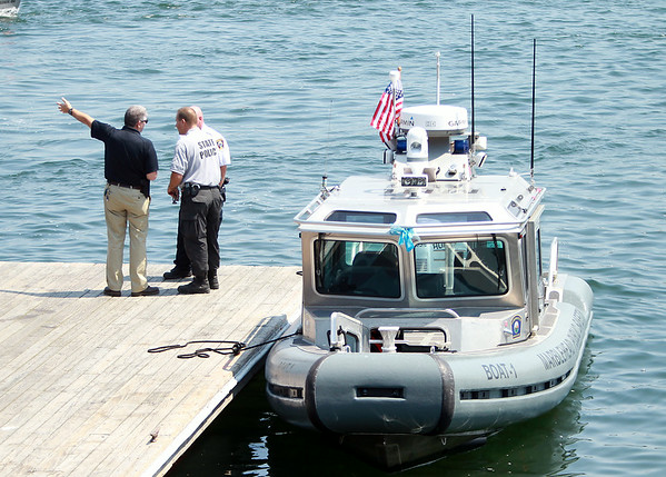 Marblehead Police Chief Robert Picariello meets with members of the Massachusetts State Police down on the docks near The Landing during an ongoing search for a missing diver off the coast of Marblehead on Tuesday afternoon. DAVID LE/Staff photo. 7/22/14.