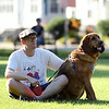 Bennett Ahearn, of Beverly, sits with his dog Rosie on the lawn of Beverly Common, listening to the tunes of Quintessential Brass on Thursday evening. DAVID LE/Staff photo. 7/10/14.