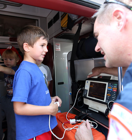 Jack Hickox, 5, of Ipswich, talks with EMT Brian Moran, of Action Ambulances, while getting his oxygen level reading at Vehicle Day at the Ipswich Public Library on Friday morning. DAVID LE/Staff photo. 7/25/14.