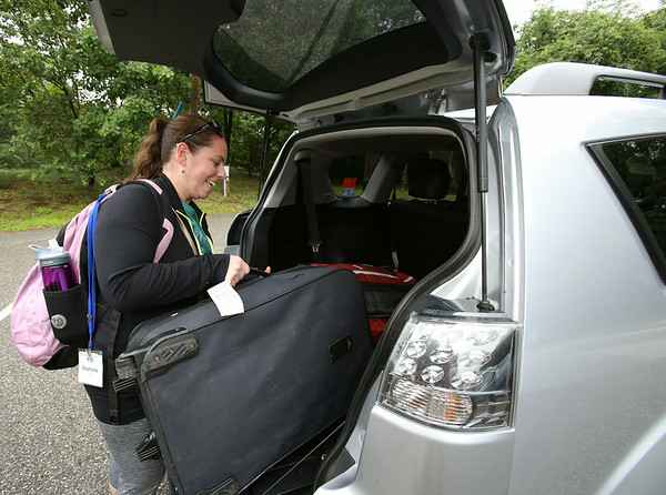 KEN YUSZKUS/Staff photo. Counselor Stephanie Band of Peabody loads her luggage into a vehicle at Temple Ner Tamid. She was with the Y2I group that traveled to Israel but the group came home early. 7/16/14