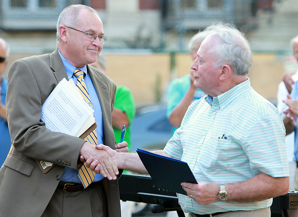 Former Beverly Mayor Bill Scanlon, right, shakes hands with former City Solicitor Roy Gelineau, after Gelineau read a statement from Congressman John Tierney during a short ceremony to dedicate a clock on Beverly Common to Scanlon's 16 years in office. DAVID LE/Staff photo. 7/9/14.