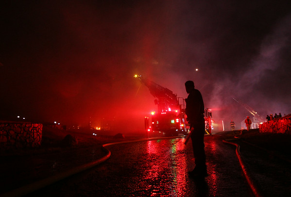 A Beverly police officer stands watch as firefighters try and battle a 3-alarm blaze on Folger Ave in Beverly on Sunday evening. DAVID LE/Staff photo. 7/13/14.