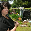 KEN YUSZKUS/Staff photo. Annmarie Schieding is in front of her daughter's grave at Oak Grove Cemetery where angels and figurines were stolen.  7/01/14