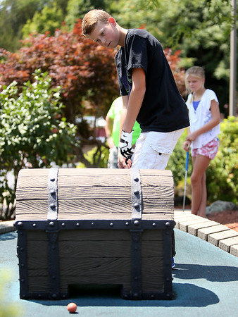 Thirteen-year-old Erik Stammnitz, of Marblehead, watches as his putt finds its way under a treasure chest obstacle in the middle of the Castle Creek mini golf course on Tuesday afternoon. DAVID LE/Staff photo. 7/29/14.