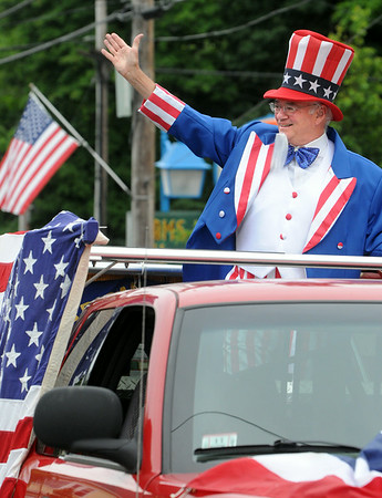 KEN YUSZKUS/Staff photo. Paul Weingartner waves to the crowd while participating in the Beverly Farms Horribles Parade. 7/4/14
