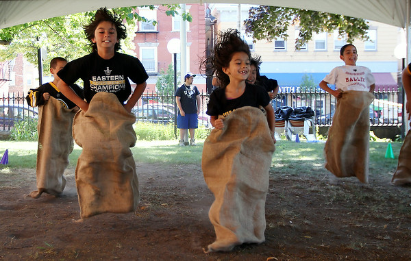 Siblings Rocco, 11, and Sofia Schirripa, 7, race against each other during a sack race at the Peabody Institute Library on Friday afternoon. DAVID LE/Staff photo. 7/11/14.