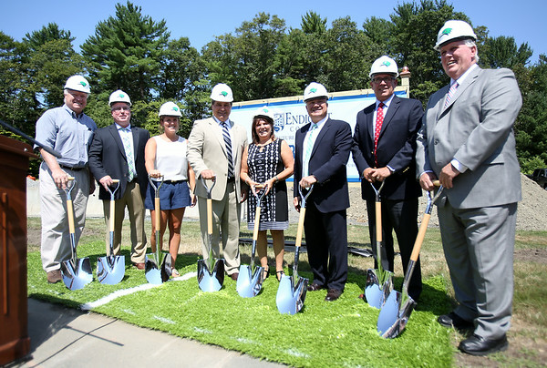 Legendary Boston Bruins defenseman Ray Bourque, and his wife Christiane, center, along with members of the Endicott College community pose for a photo at a groundbreaking ceremony for the new ice hockey rink to be built on campus and will be named in Bourque's honor. DAVID LE/Staff photo. 7/29/14.