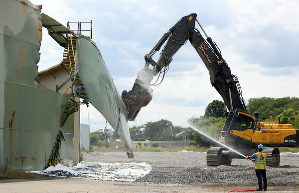 An excavator with a shearing mechanism attached, operated by a member of JDC Demolition, rips off a portion of the outer wall of the B5 tank, an old oil tank inside the Salem Power Plant facility on Wednesday afternoon. The B5 tank is the first of the old oil tanks on the site to be taken down and will take approximately two weeks until it is completely gone. DAVID LE/Staff photo. 7/30/14.