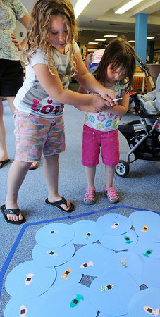 KEN YUSZKUS/Staff photo. Madison Irwin,6, left, of Beverly, helps her cousin Abby Troisi, 3, of Peabody catch a fish at the Magnet Fish game at the Fizz, Boom, Party held at the Salem Public Library. 7/2/14