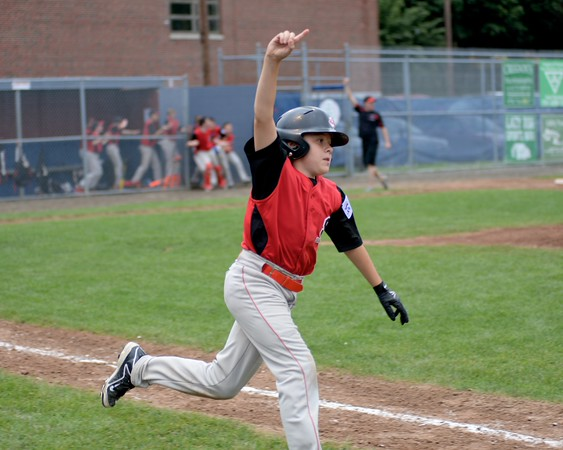 RYAN HUTTON/ Staff photo<br /> Salem's William Foglietta raises his arm in victory as he heads to first base after hitting the winning home run in the bottom of the fourth inning of Wednesday's District 16 Championship game against Saugus American. Salem won 18-8.