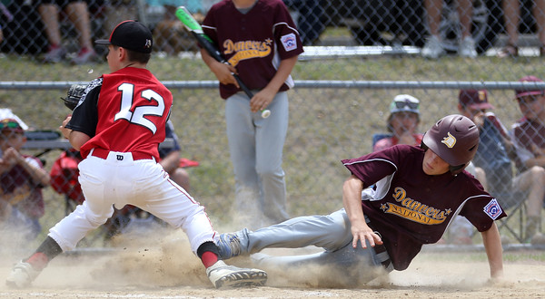 DAVID LE/Staff photo. Danvers National's Cameron Wodarski slides safely home on a wild pitch as Amesbury pitcher Drew MacDonald waits for the throw. 7/2/16.