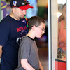 DAVID LE/Staff photo. Twelve-year-old Tyler Cushing, of Reading, with help from his father Chris, tries to win coins from an arcade game at the Salem Willows Arcade on Monday afternoon. 7/25/16.