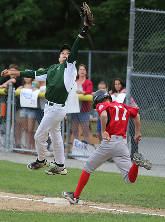 KEN YUSZKUS/Staff photo.  Boxford-Topsfield's Nick Cantalupo gets on 1st as Manchester Essex's Thomas Steriti jumps, but misses the throw during the Boxford-Topsfield vs. Manchester Essex Little League playoff game at Harry Ball Field in Beverly.    07/11/16