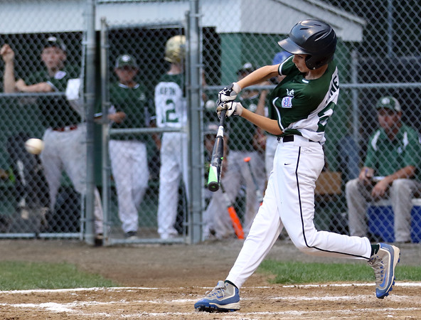 DAVID LE/Staff photo. Manchester-Essex right fielder Kellan Heney lines a single against Beverly in the District 15 Final on Thursday evening. 7/14/16.