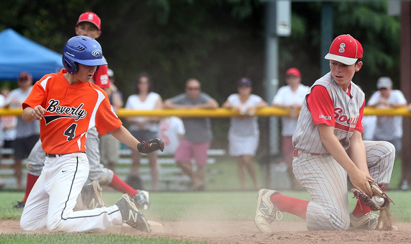DAVID LE/Staff photo. Beverly's Joe Brown kneels safely on second after advancing on a double play attempt overthrow. 7/28/16.