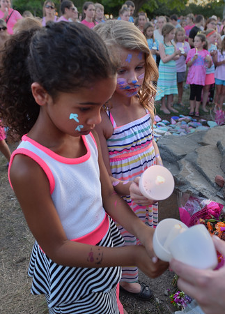 Lylah Saunders (l) and Mya Dexter of Salem light candles in memory of Riley Fessenden at the Riley Rocks event at Lynch Park.<br /> <br /> Photo by joebrownphotos.com