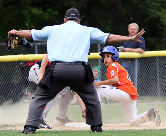 DAVID LE/Staff photo. Beverly's Dom Santos looks back at the umpire as he signals safe on a close play at third. 7/8/16.