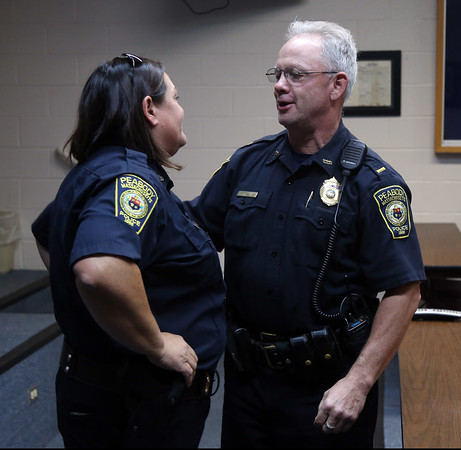 DAVID LE/Staff photo. Peabody Police Lt. Buddy Yeo smiles and talks with retiring police officer Nancy Hart after a short ceremony on Friday afternoon. 7/22/16.