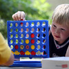 DAVID LE/Staff photo. Nine-year-old Henry Carlson-Lier places a red chip into a slot while playing Connect Four against Roark Mullins at WaringWorks at the Waring School on Wednesday afternoon. 7/20/16.
