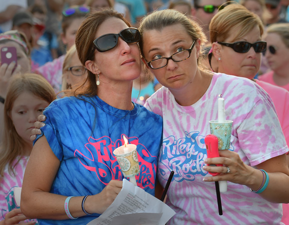 Kate Bennett (l) and Jennifer Burnett console each other during the reading of a poem dedicated to Riley at the Riley Rocks event at Lynch Park.<br /> <br /> Photo by joebrownphotos.com