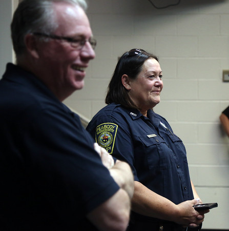 DAVID LE/Staff photo. Retiring Peabody Police officer Nancy Hart and Peabody Police Chief Tom Griffin smile while listening to Lt. Sheila McDaid thank Hart for their friendship and service together as the first two women in the Peabody Police Department. Hart is retiring after over 25 years in service. 7/22/16.