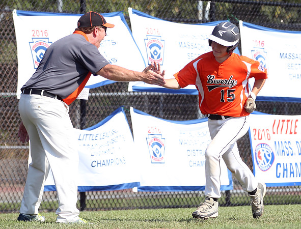DAVID LE/Staff photo. Beverly's Joey Loreti gets a high five from manager Brady Frost as he rounds third after launching a homer. 7/29/16.