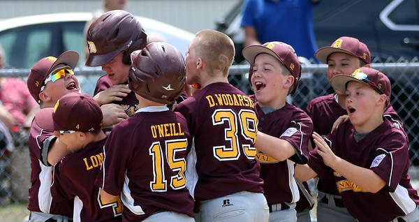DAVID LE/Staff photo. Danvers National first baseman Nolan Hills is mobbed by his teammates after launching a homer against Amesbury. 7/2/16.