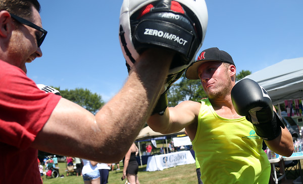 DAVID LE/Staff photo. Jeff Stern, of Marblehead, tries his hand at boxing as he spars with Sean Nichols, of Title Boxing in Saugus at Paddle for Plummer on Saturday morning. 7/16/16.