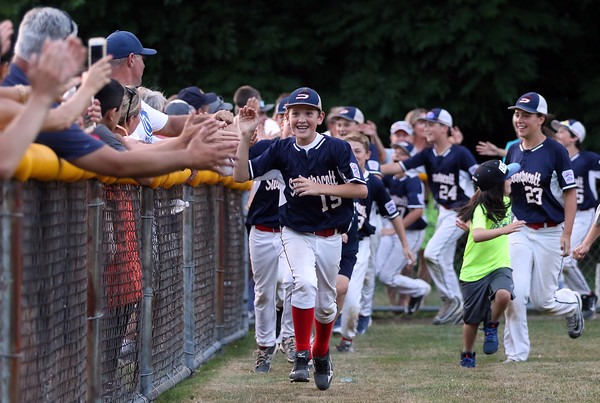 DAVID LE/Staff photo. Swampscott's Nathan DeRoche leads a victory lap around the field after Swampscott defeated Peabody West 10-7 in the District 16 Championship. 7/15/16.