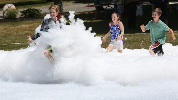 KEN YUSZKUS/Staff photo.   Children run into the foam sprayed by the fire department at the Firemen's Muster at Endicott Park in Danvers.   07/06/16