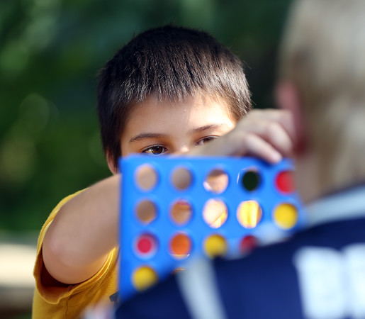 DAVID LE/Staff photo. Roark Mullins, 13, strategically places a Connect Four piece into a slot while playing against Henry Carlson-Lier, at WaringWorks at the Waring School on Wednesday afternoon. 7/20/16.