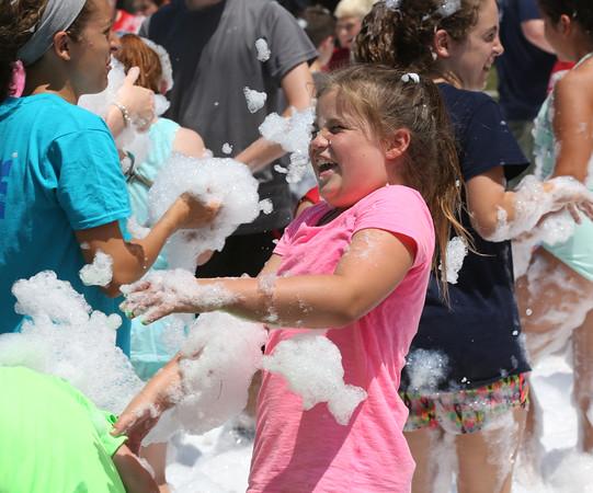 KEN YUSZKUS/Staff photo.   Avery Maynard reacts as foam is thrown toward her at the Firemen's Muster at Endicott Park in Danvers.   07/06/16